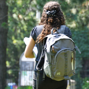 A student carrying a backpack walks along campus