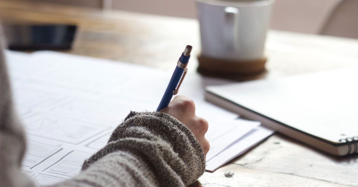 Une personne se penche sur ses travaux, crayon à la main