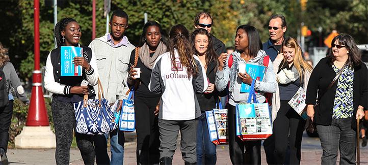 Groupe de gens suivent une visite guidée sur le campus.