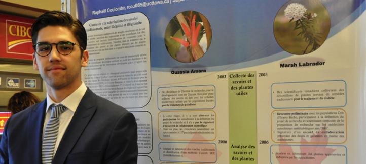 Raphaël Coulombe devant son affiche au symposium du PIRPC