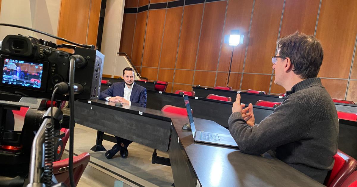 Deux hommes s'entretiennent devant la caméra dans une salle de cours, à quelques sièges de distance