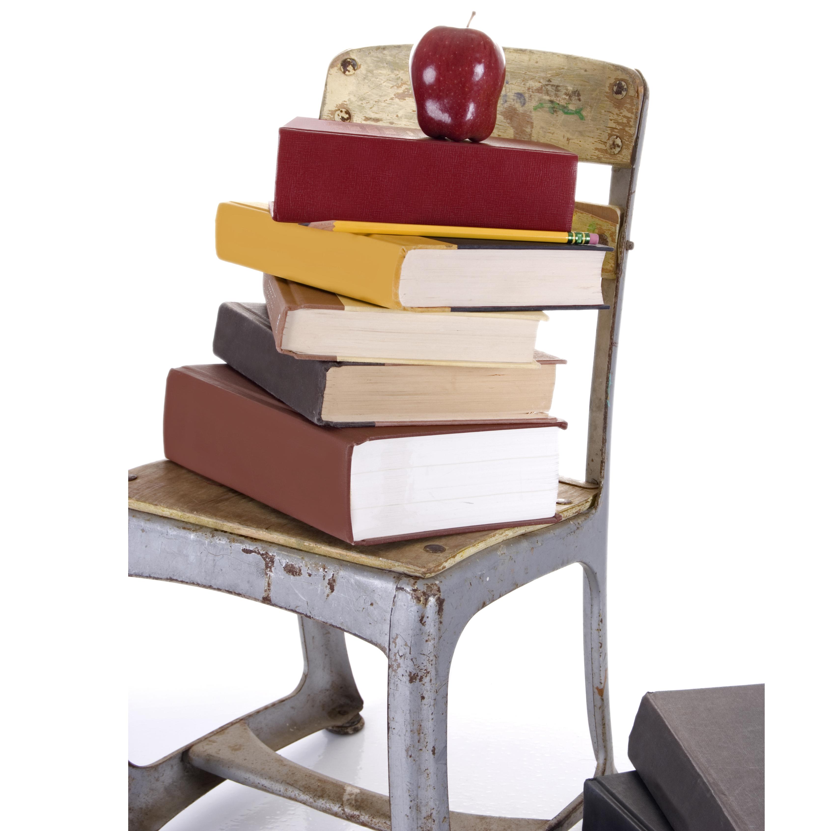 Chaise d'écolier et pomme sur pile de livres