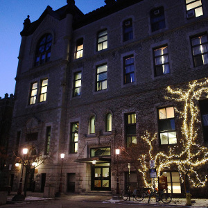 Academic Hall's exterior decorative lights brighten a snow-covered campus at twilight during the Christmas Lights Ceremony