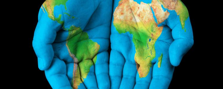 Deux mains en formes d'une coupe sur lesquelles on a peinturé une carte du monde