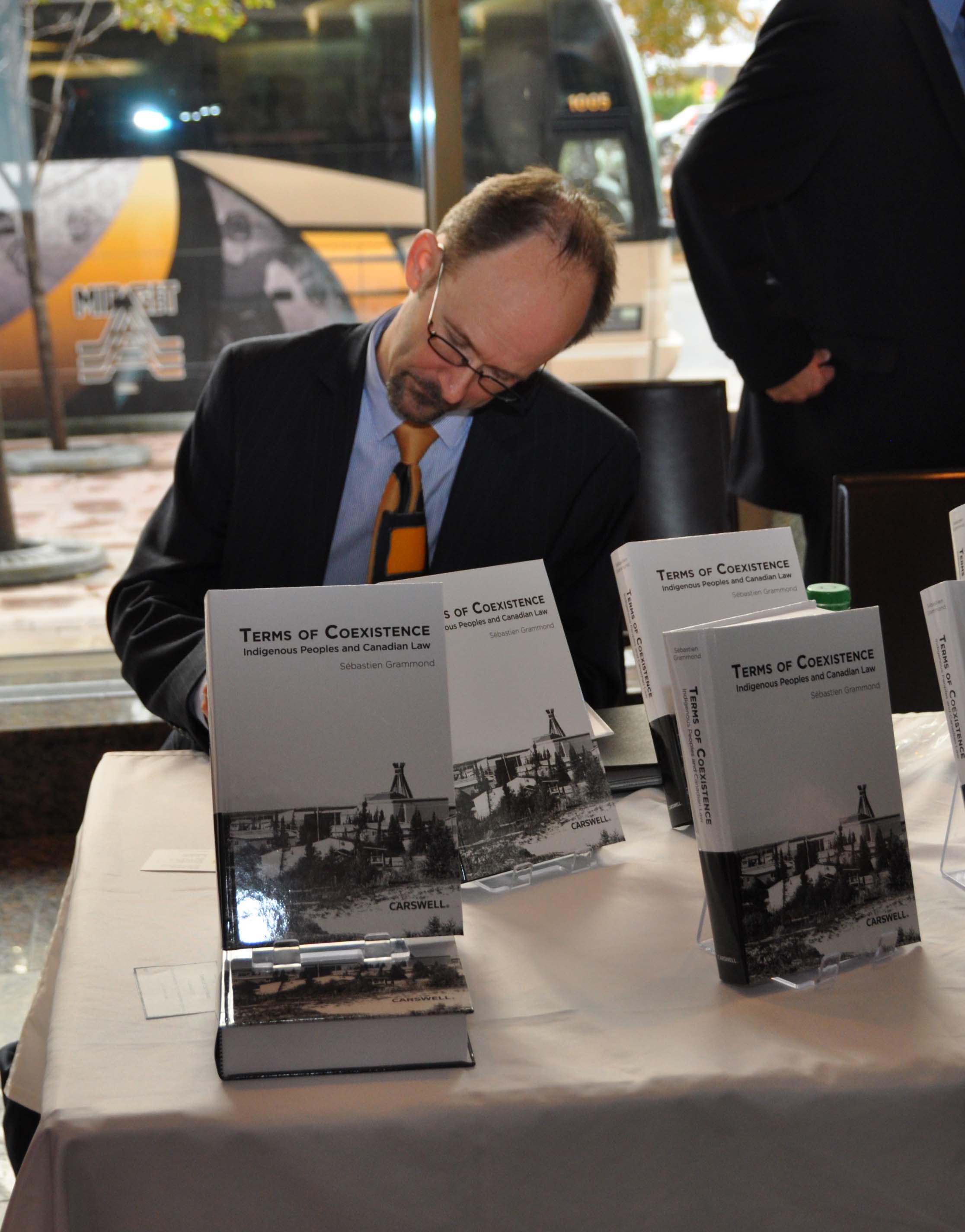 Le doyen Grammond signe une copie de son ouvrage pour un collègue.