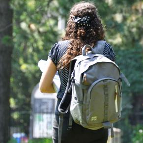 Une étudiante avec un sac à dos marche sur le campus